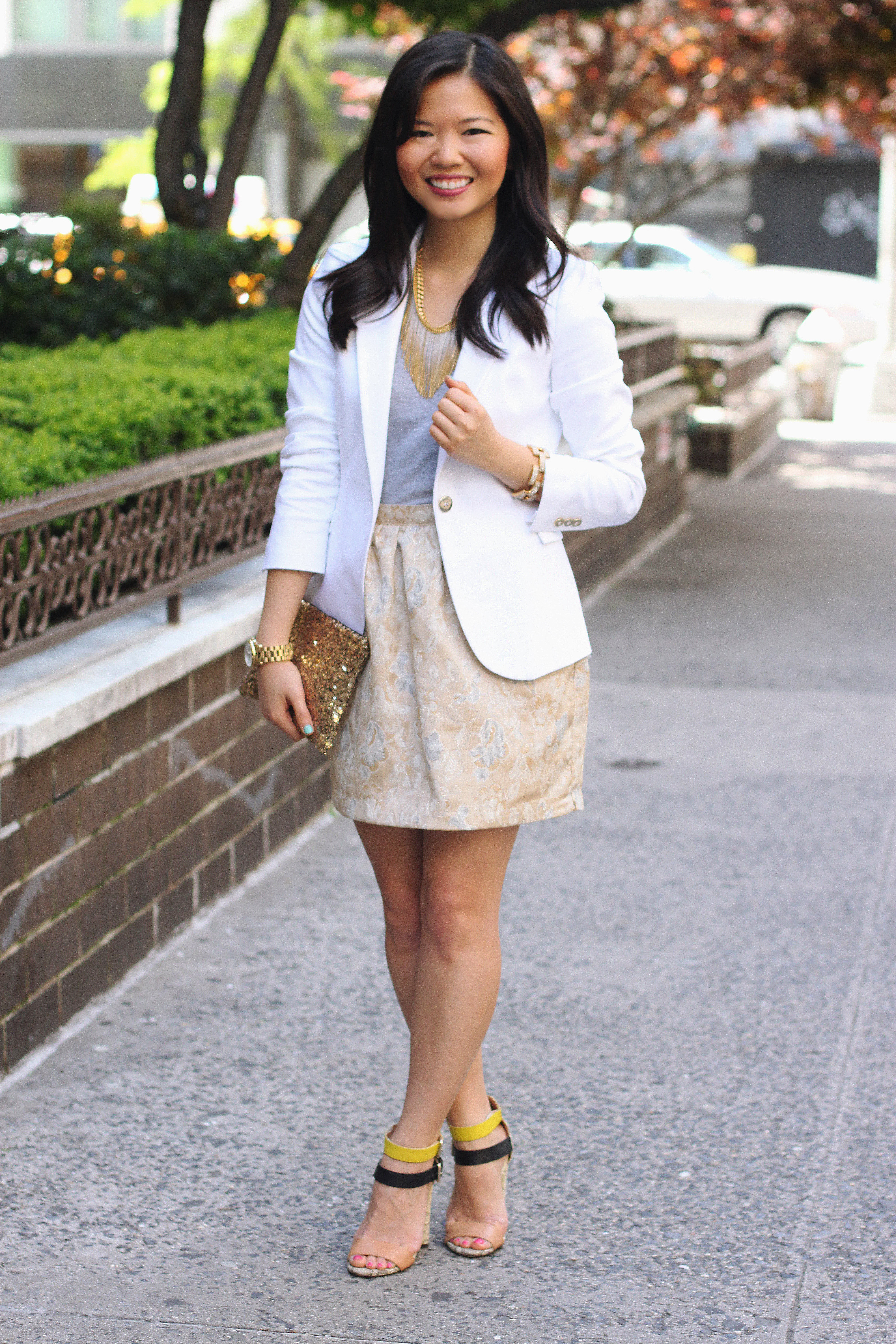 Skirt The Rules Blog; NYC fashion blogger; style blog; spring outfit photos; Zara white blazer with gold buttons; H&M gray v-neck t-shirt; Forever 21 gold gray floral skirt; Juicy Couture fringe necklace; Hello Fab gold glam clutch; J.Crew gold pave square link bracelet; Zara neon snakeskin heels with buckles; Michael Kors mother of pearl gold boyfriend watch