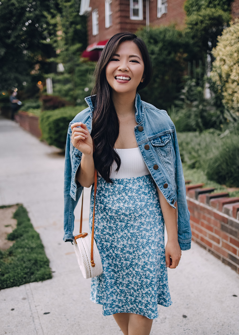 Casual Spring Outfit for Women: Denim Jacket, White Bodysuit, Blue Floral Midi Skirt, White Straw Circle Bag, White Leather Sneakers